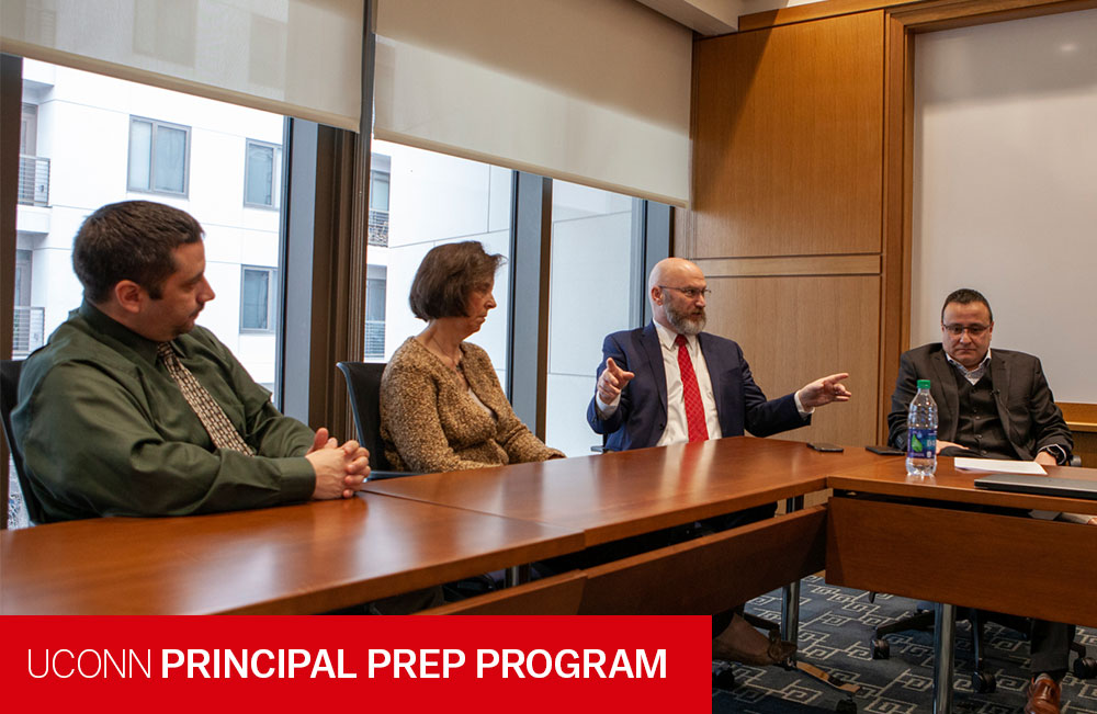 Dr. Richard Gonzales at a conference table with three other UPPI affiliates.  Text reads: UConn Principal Prep Program.  Photo Credit: Wallace Foundation