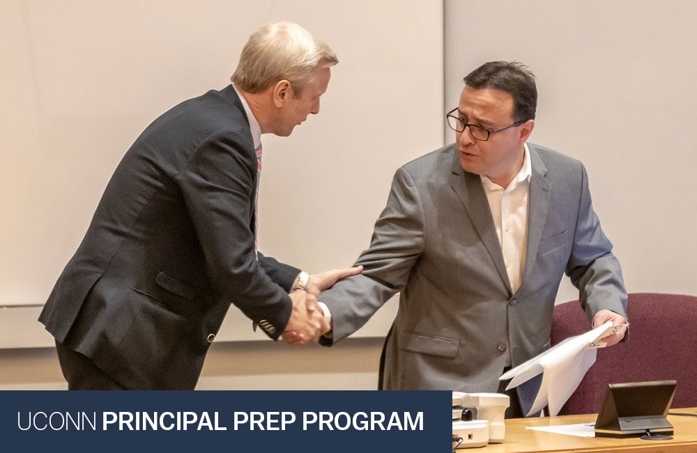 Dr. Richard Gonzales shaking hands with a UPPI affiliate.  Text reads: UConn Principal Prep Program.  Photo credit: Wallace Foundation