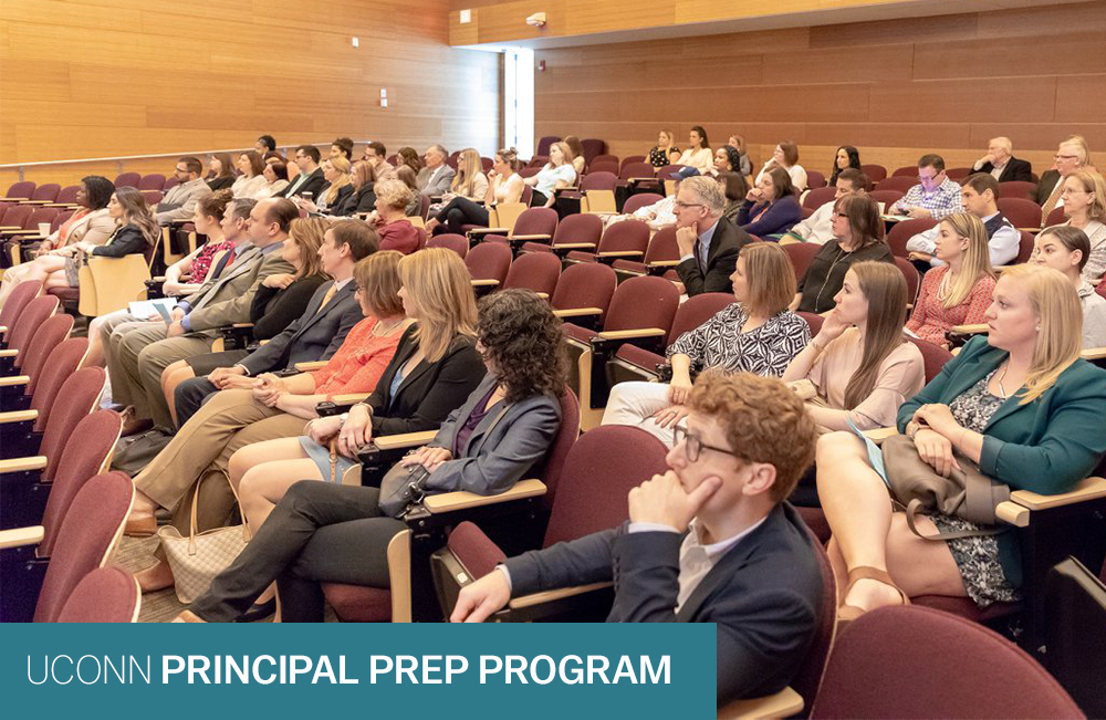 Auditorium filled room of students listening.  Text reads: UConn Principal Prep Program.  Photo credit: Wallace Foundation