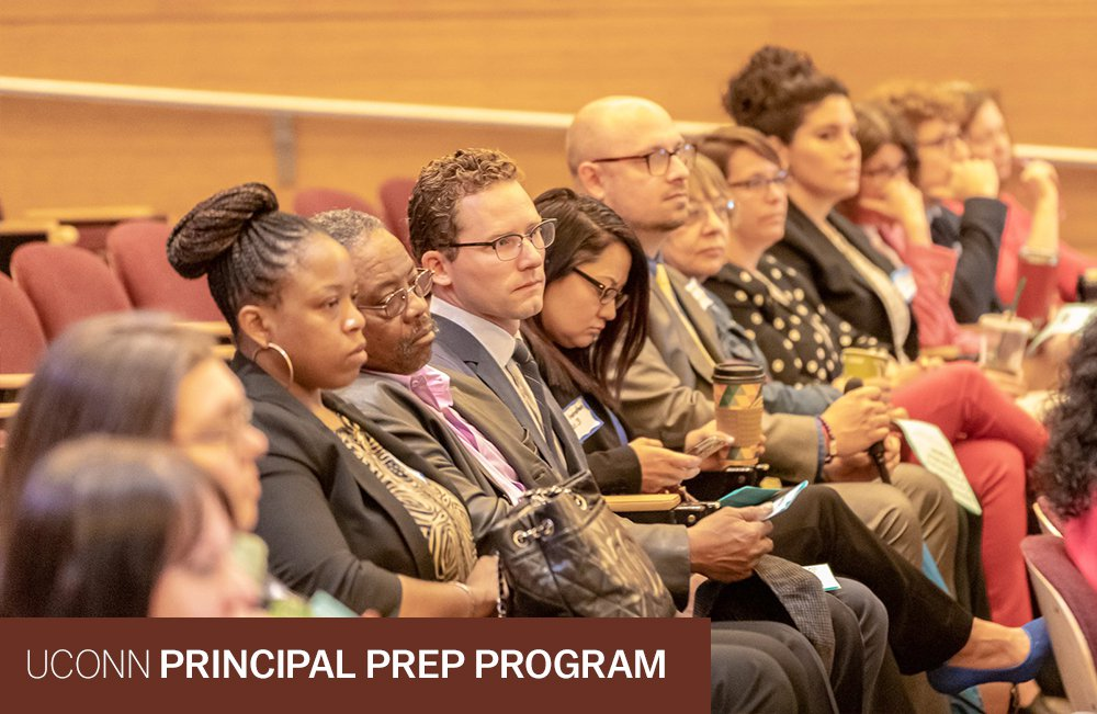 Snapshot of students listening to a presentation from their seats.  Text reads: UConn Principal Prep Program.  Photo credit: Wallace Foundation