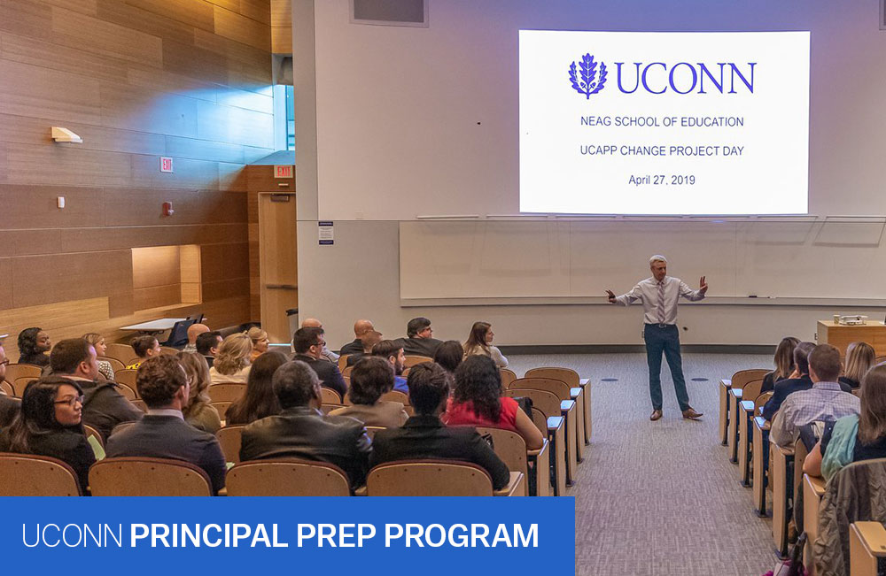 UPPI instructor presenting in an auditorium during the 2019 UCAPP Change Project Day. Text reads: UConn Principal Prep Program. Photo credit: Wallace Foundation